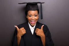 El graduado de universidad manosea con los dedos para arriba Imagen de archivo libre de regalías