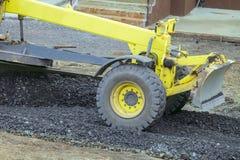 El graduador movible del motor con una cuchilla realiza la disposición de una base de piedra machacada camino de la grava Imagen de archivo