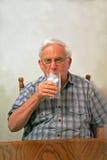 El Grandpa bebe el agua de hielo imagen de archivo libre de regalías