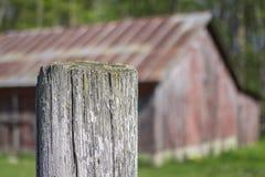 El granero rojo viejo borroso en fondo con blanco se descoloró los posts i de la cerca Imagen de archivo