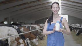 El granjero bonito joven de la muchacha que mostraba con buena calidad de la sonrisa certificó la leche en granja con las vacas metrajes
