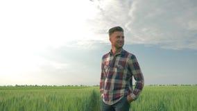 El granjero camina con campo verde de la cebada y disfrutar del aire fresco y de la belleza de la naturaleza en fondo del cielo a metrajes