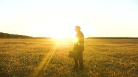 El granjero camina a trav?s de campo Agr?nomo que camina en campo por la tarde El hombre de negocios camina a trav?s de parque en metrajes