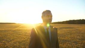 El granjero camina a trav?s de campo hombre de negocios con la cartera negra que camina a trav?s de campo en rayos del sol brilla metrajes