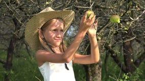 El granjero Child en el manzanar, prueba de la muchacha del país da fruto en árbol en el pueblo 4K