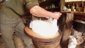 El granjero da el queso caliente de los paquetes en la estopilla para la cabaña de los pastores de la deshidratación