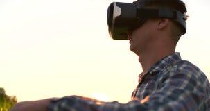 El granjero de sexo masculino en vidrios de la realidad virtual en el campo en la puesta del sol controla el sistema de irrigació almacen de metraje de vídeo