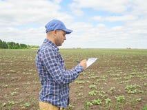 El granjero en camisa de tela escocesa controló sus notas del campo y de la escritura Foto de archivo libre de regalías
