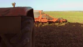 El granjero en tractor ara el suelo de la agricultura del movimiento del steadicam de Rusia la tierra preparada de tierra con el  metrajes