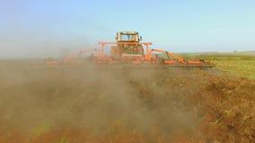 El granjero en tractor ara el suelo de la agricultura del movimiento del steadicam de Rusia la tierra preparada de tierra con el  almacen de metraje de vídeo