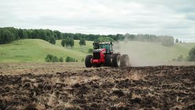 El granjero en tractor prepara la tierra con el cultivador del semillero en la estación de primavera temprana de trabajos agrícol almacen de metraje de vídeo