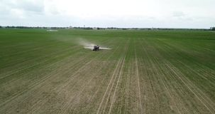 El granjero en un tractor con un rociador hace el fertilizante metrajes