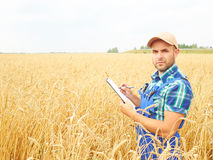 El granjero en una camisa de tela escocesa controló sus notas del campo y de la escritura Imágenes de archivo libres de regalías