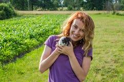 El granjero encantador joven de la mujer con el pelo largo en una camisa, en un pueblo en su jardín camina llevando a cabo las ma Foto de archivo