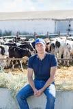 El granjero está trabajando en granja con las vacas lecheras Foto de archivo libre de regalías