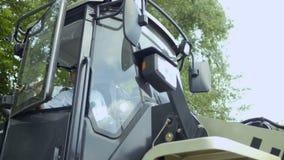 El granjero examina el tractor desde adentro de la cabina almacen de video