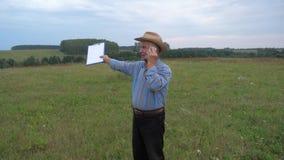 El granjero mayor In Cowboy Hat que se coloca en el campo, habla en el teléfono almacen de metraje de vídeo