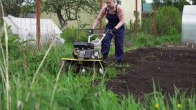 El granjero muscular rubio joven cultiva el suelo de tierra con la mini sierpe rotatoria almacen de metraje de vídeo