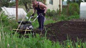 El granjero muscular rubio joven cultiva el suelo de tierra con la mini sierpe rotatoria metrajes