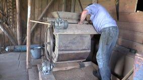 El granjero procesó el grano con la arpa de limpiamiento del gato viejo en granero almacen de video