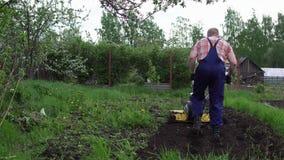 El granjero rasga la tierra con un cultivador metrajes