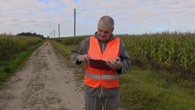 El granjero sale en el camino del campo de maíz metrajes