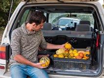 El granjero se sienta en el tronco de un coche con la cosecha de la calabaza de otoño imágenes de archivo libres de regalías