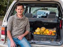 El granjero se sienta en el tronco de un coche con la cosecha de la calabaza de otoño imagenes de archivo