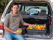 El granjero se sienta en el tronco de un coche con la cosecha de la calabaza de otoño fotos de archivo libres de regalías
