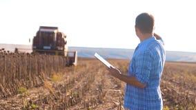 El granjero trabaja el girasol agrícola elegante de la lectura del hombre o de la cosecha del análisis una forma de vida del info metrajes