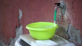 El grifo de agua llena el lavabo a desbordar metrajes