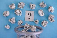 El gris arrugó las bolas de papel y el desarrollo del signo de interrogación de un tra Fotografía de archivo libre de regalías