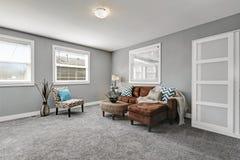 El gris entona sala de estar con el sofá marrón cómodo Fotos de archivo libres de regalías