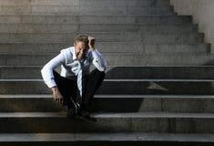 El griterío del hombre de negocios perdió en la depresión que se sentaba en las escaleras del hormigón de la calle Fotografía de archivo libre de regalías