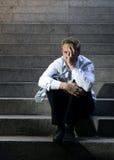 El griterío del hombre de negocios perdió en la depresión que se sentaba en las escaleras del hormigón de la calle Imagenes de archivo