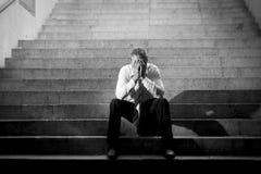 El griterío del hombre de negocios perdió en la depresión que se sentaba en las escaleras del hormigón de la calle Imagen de archivo libre de regalías