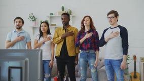 El grupo étnico multi de aficionados deportivos de los amigos que canta himno nacional antes de mirar se divierte campeonato en l almacen de video