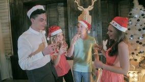 El grupo alegre de amigos cerca de la Navidad adornó el árbol, alcohol de la bebida de las copas de vino - riendo, divirtiéndose metrajes
