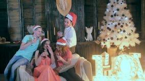 El grupo alegre de amigos cerca de la Navidad adornó el árbol, alcohol de la bebida de las copas de vino - riendo, divirtiéndose almacen de metraje de vídeo
