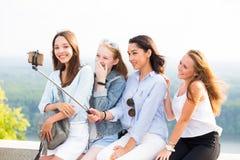 El grupo alegre de mujeres sonrientes jovenes hace un selfie en el fondo de la naturaleza fotos de archivo