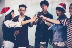 El grupo asiático de amigos que tienen partido con la cerveza alcohólica bebe a Imagenes de archivo