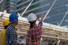 El grupo asiático de los ingenieros consulta la construcción en trabajo del edificio del sitio imágenes de archivo libres de regalías