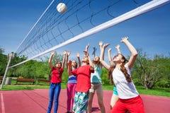 El grupo de adolescencias con los brazos sube voleibol del juego Imágenes de archivo libres de regalías
