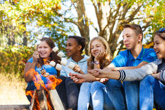 El grupo de adolescencias sostiene los palillos de la melcocha cerca de la llama Imágenes de archivo libres de regalías