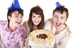 El grupo de adolescente con la torta celebra feliz cumpleaños. Foto de archivo