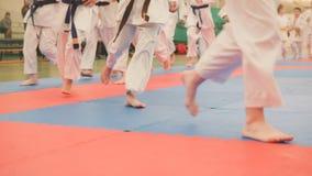 El grupo de adolescentes de los deportistas del karate en kimono corre en tatami en el gimnasio Foto de archivo