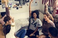 El grupo de adolescentes en un dormitorio arma concepto aumentado de la comunidad y del trabajo en equipo Imagenes de archivo