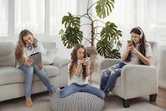 El grupo de adolescentes está utilizando los artilugios Niños con los teléfonos y tabletas, smartphones y auriculares Foto de archivo libre de regalías