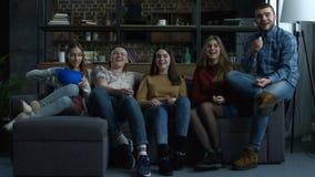 El grupo de adolescentes mira película del comdey con palomitas almacen de video