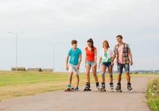 El grupo de adolescentes sonrientes con patina sobre ruedas Fotografía de archivo